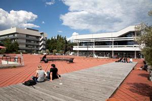 Studierende sitzen auf dem roten Platz der TechFak
