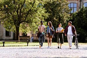 Studierende spazieren in einem Park und unterhalten sich