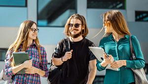 Studierende unterhalten sich vor einem Gebäude