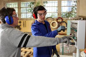 Studierender lernt die Bedienung einer Maschine im Praktikum