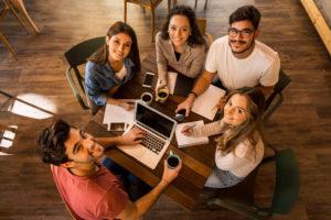 Junge Leute sitzen um einen Tisch und schauen nach oben in die Kamera