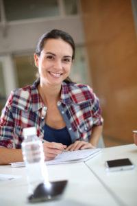 Studentin schaut in Kamera und lächelt